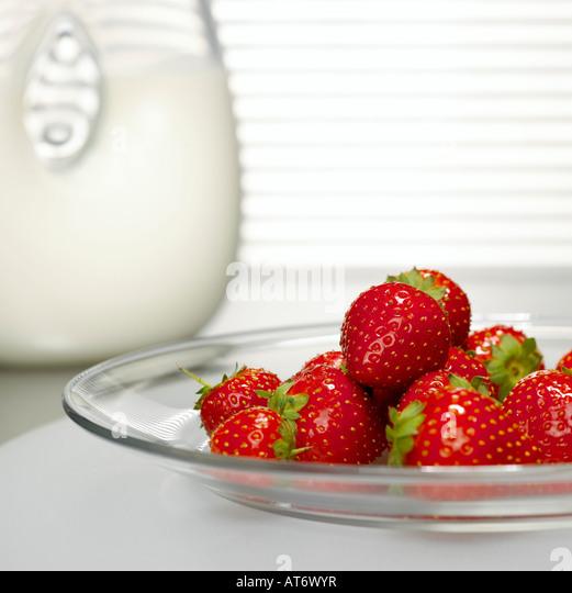 Erdbeeren auf Glasplatte vor Milch Glas, Nahaufnahme Stockbild