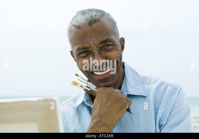 Ältere Mann, der Lack hält Pinsel im Freien, in die Kamera Lächeln, Leinwand im Vordergrund Stockbild