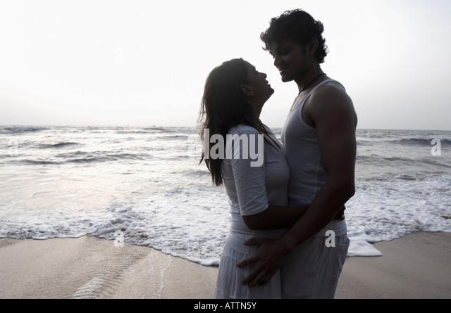 Silhouette eines jungen Paares umarmen einander am Strand, Goa, Indien Stockbild
