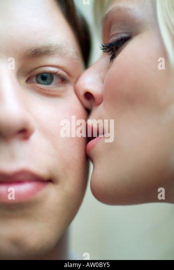 Nahaufnahme von junge Frau Mann auf Wange küssen Stockbild