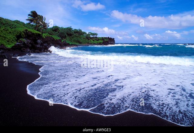 Schwarzen Sand Strand und Surfen im Waianapanapa State Park in der Nähe von Hana Maui Hawaii Stockbild