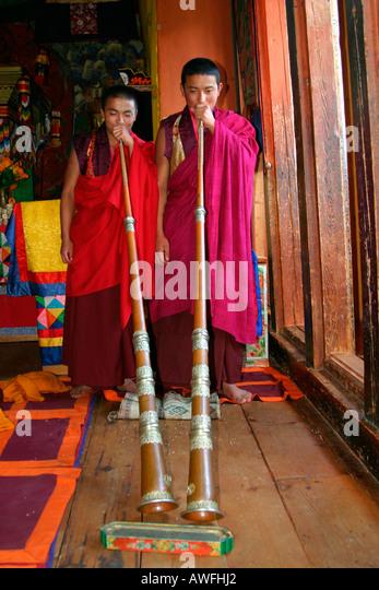 Zwei Mönche, die ihre traditionelle Trompete, Bhutan Stockbild