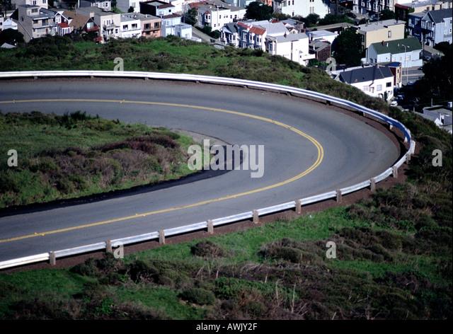 Kurve der Straße mit Häusern unten. Stockbild
