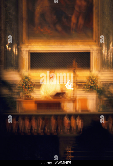 Priester hinter dem Altar, unscharf Stockbild
