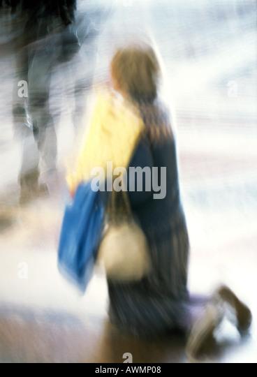 Frau kniend, verschwommen Stockbild
