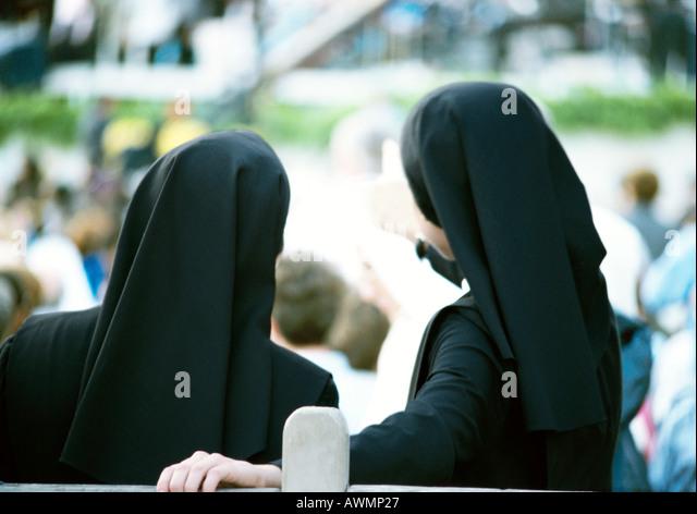 Zwei Nonnen stehen Seite an Seite Rückansicht mit Blick auf Masse, Stockbild