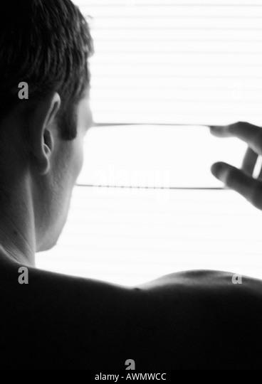 Mann sucht durch Jalousien, Sicht nach hinten, Kopf und Schultern, Teilansicht, schwarz und weiß. Stockbild