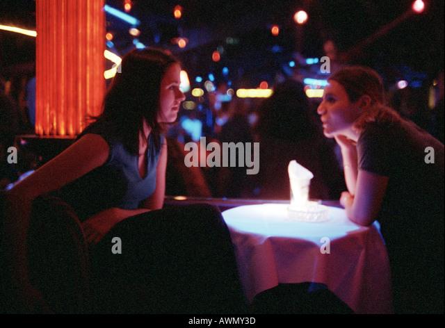 Junger Mann und Frau sitzen in bar, Gespräch am Tisch, dramatische Beleuchtung. Stockbild