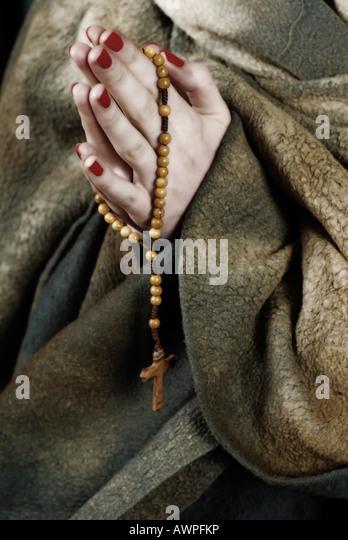 Betende Hände in Gewohnheit mit Rosenkranz Stockbild