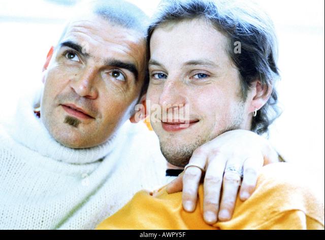 Zwei Männer sitzen, Arm des Mannes um die andere Hals, Porträt. Stockbild