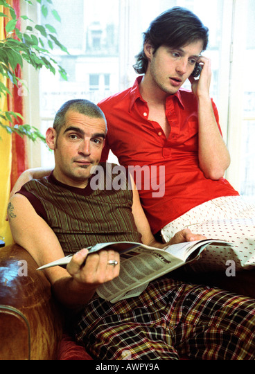 Zwei Männer sitzen, ein Blick in die Kamera, Zeitung, mit einem Handy. Stockbild
