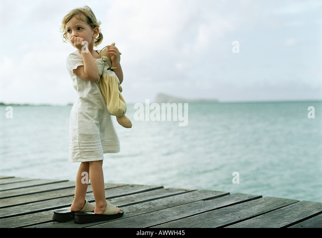 Kleines Mädchen stand auf Dock, Daumenlutschen und sah über die Schulter Stockbild