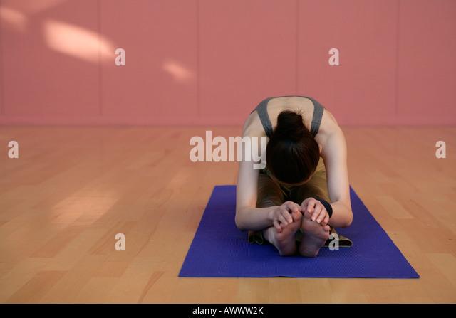 Junge Frau, die Dehnung auf Yoga-Matte Stockbild