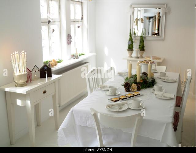 Kuchen mit Kerzen und Tannenzapfen am Esstisch Stockbild