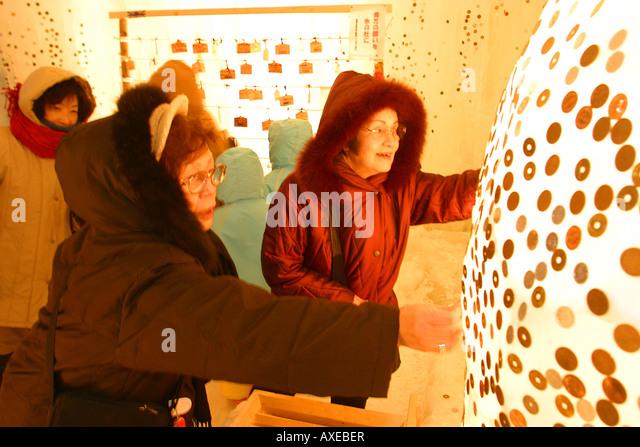 Setzen die Münzen auf dem Eis als Glücksbringer bei Sounkyo Ice Festival Stockbild
