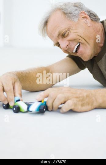 Reifer Mann auf dem Boden, spielen mit Spielzeug-Autos, lächelnd, Nahaufnahme Stockbild