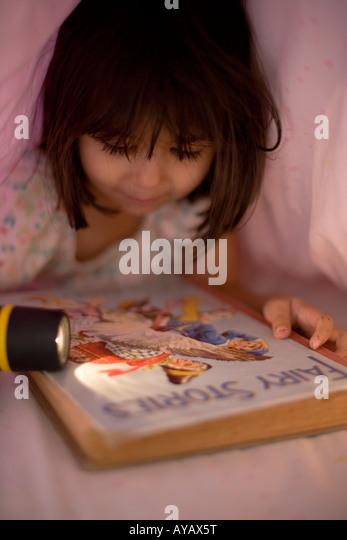 Lesen unter der Bettdecke bei Fackelschein Stockbild