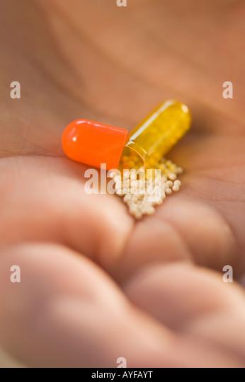 Nahaufnahme eines offenen Medikamente Kapsel in die Hand des Menschen Stockbild