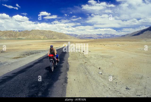 Radfahrer tragen Kopfbedeckung mit voll beladenen Fahrrad auf einer einsamen Strecke von Wüste, Ladakh, Indien Stockbild
