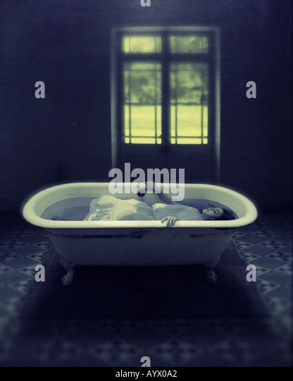 Mädchen im weißen Kleid, die untergetaucht im Wasser in Badewanne im leeren Raum mit Tür zum Garten Stockbild