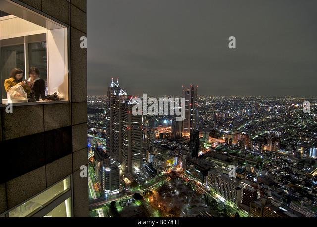 Japanisches paar Blick auf Tokio bei Nacht. Beleuchtete Stadtbild von der 42. Etage. Shinjuku, Tokio, Japan Stockbild