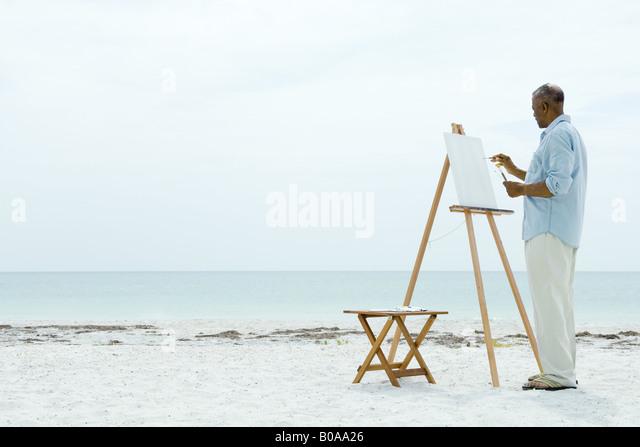 Senior woman malen auf Leinwand am Strand, Seitenansicht Stockbild