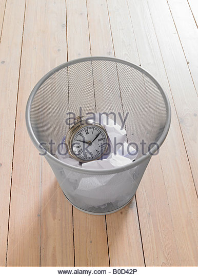 Veraltete Uhr im Papierkorb Stockbild