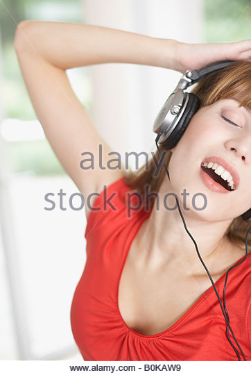Frau trägt Kopfhörer und tanzen Stockbild