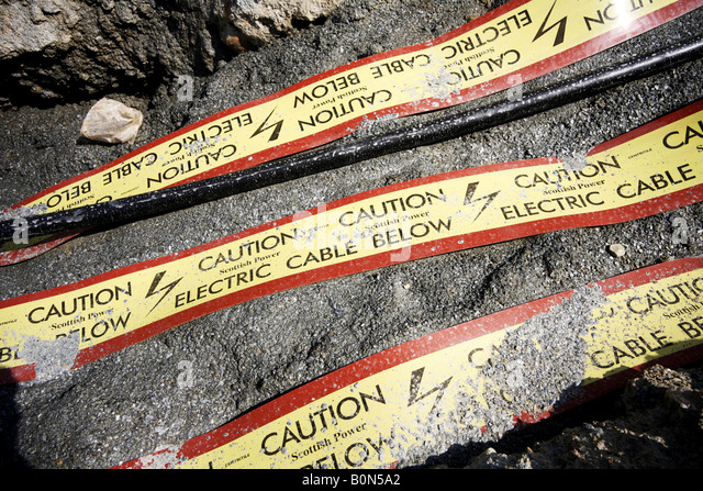 Stromkabel in am Straßenrand Graben Warnbändern im Boden Vorsicht Eelectric Kabel ausgesetzt Stockbild