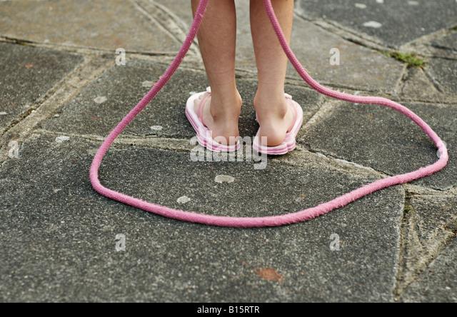 Kind mit rosa Springseil Stockbild