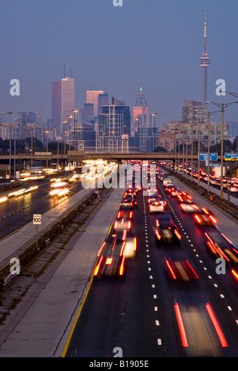 Feierabendverkehr auf QEW (Queen Elizabeth Way) und Skyline von Toronto, Toronto, Ontario, Kanada. Stockbild
