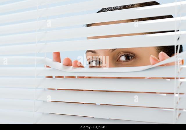 Frau auf der Suche aber Jalousien Stockbild