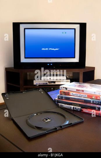 Ein Haufen von DVD-Filmen mit Fernseher und DVD-Player im Hintergrund Stockbild