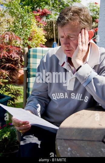 Reifer Mann sitzt an einem Tisch und liest Papierkram Stockbild