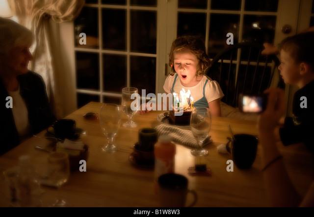 Sieben Jahre altes Mädchen bläst die Kerzen auf ihrem Geburtstagskuchen Stockbild