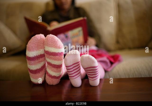 Indische Mutter der 30er Jahre und Mischlinge Tochter 4 lesen Sie ein Buch rosa gestreifte Socken Stockbild