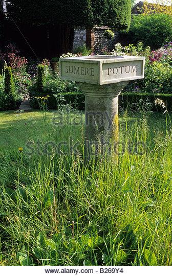 Gärtner s Cottage Sussex Vogeltränke auf grasbewachsenen Hügel mit lateinischen Inschrift Stockbild