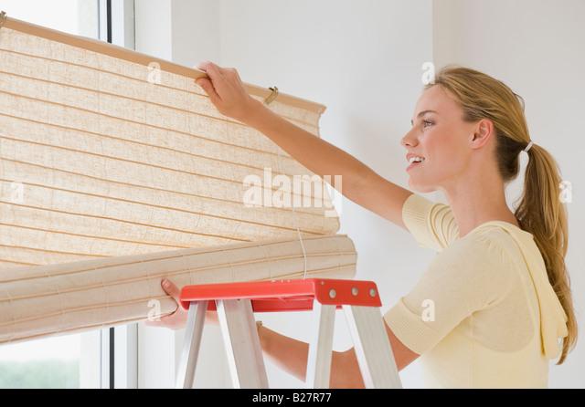 Frau Fenster hängen Vorhänge Stockbild