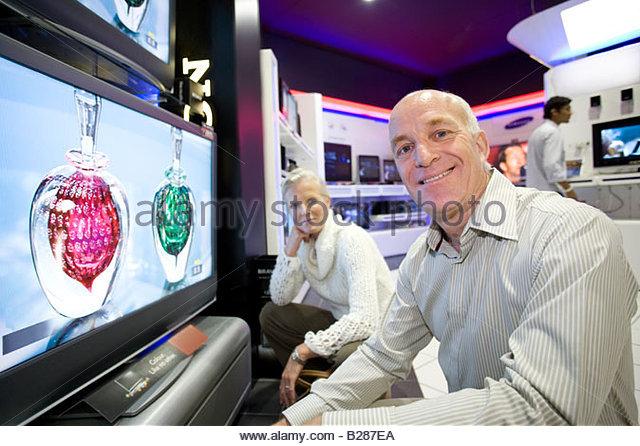 Älteres Paar mit Flachbildschirm im Elektronik-Shop, Porträt Stockbild
