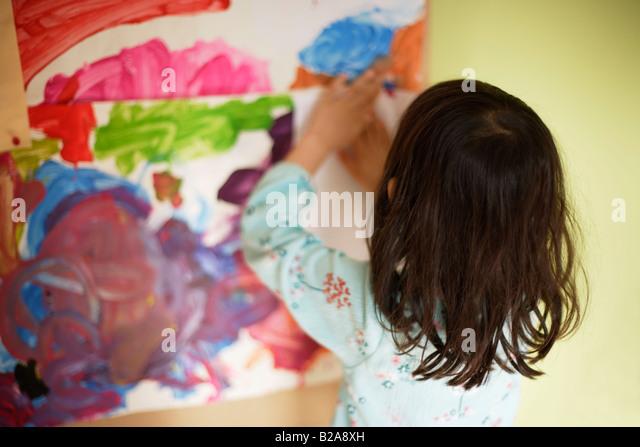 Fünf Jahre altes Mädchen klebt Kunstwerke auf ihr Schlafzimmer Pinnwand Mischlinge indischen ethnischen Stockbild