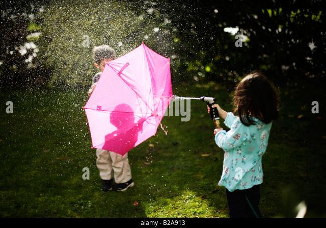 Jungen im Alter von sechs Jahren Unterstände hinter rosa Regenschirm Stockbild