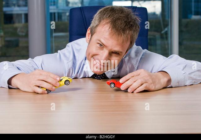 Porträt der Geschäftsmann mit Spielzeugautos spielen Stockbild