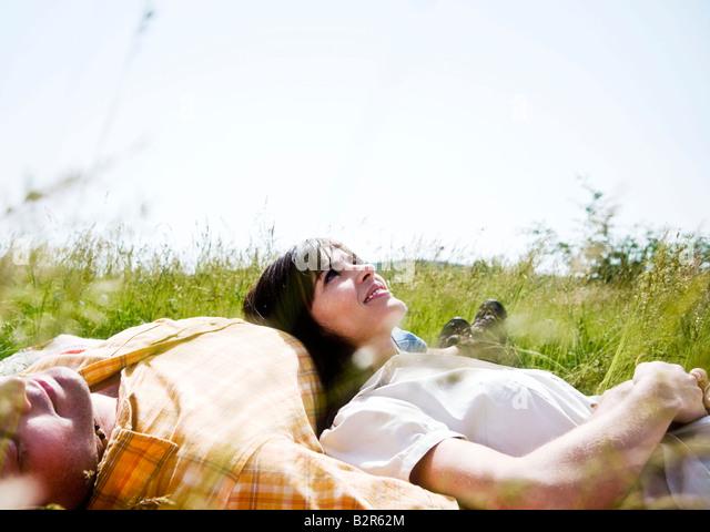 Mann und Frau im Gras liegen Stockbild