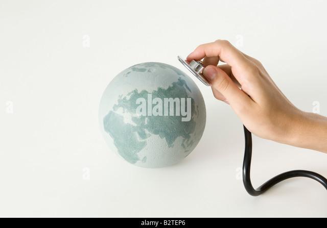 Hand mit Stethoskop bis zu Globus, beschnitten Stockbild