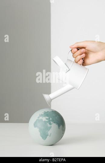 Hand, die Gießkanne über Globus Stockbild
