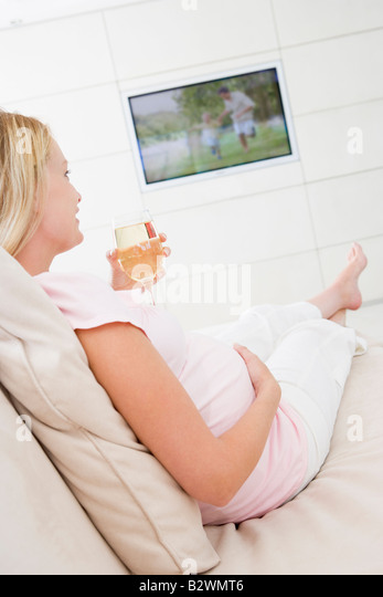Schwangere Frau vor dem Fernseher mit Glas Weißwein Stockbild