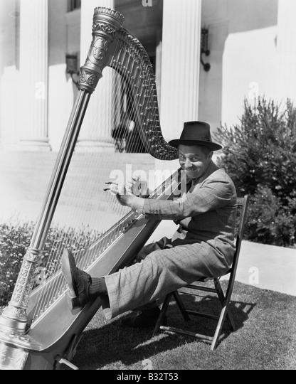 Profil von einem Mann spielt eine Harfe und lächelnd Stockbild