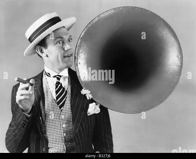 Mann hält eine Zigarre und stand in der Nähe ein Victrola-horn Stockbild