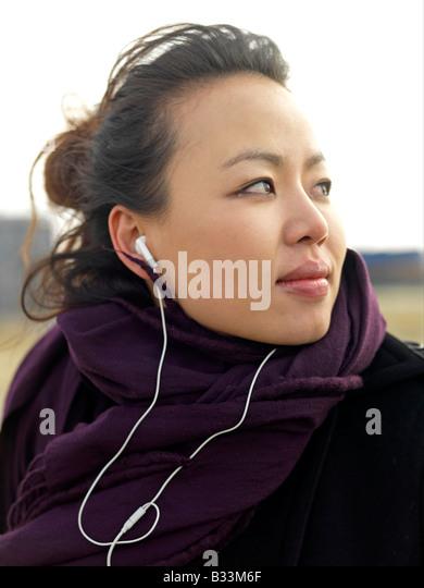 Eine junge Frau mit Wind fegte schaut Weg, während Sie Musik hören. Stockbild