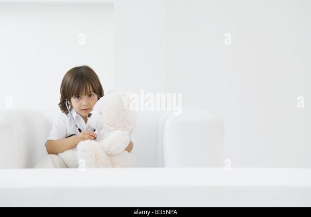 Kleiner Junge spielt Arzt mit Teddybär, mit Stethoskop Stockbild